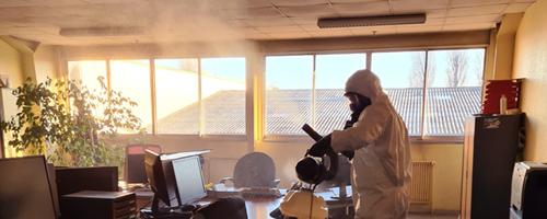 Technicien désinfectant un bureau de la covid-19